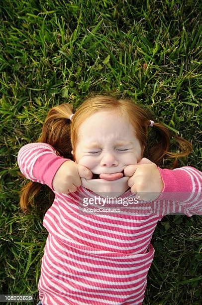 Kleines Mädchen machen lustige Gesicht und liegen im Gras
