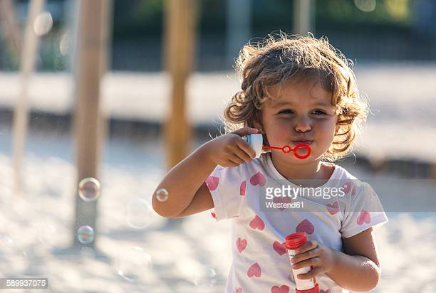 Little girl making soap bubbles at playground