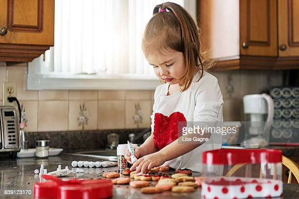 Little girl making valentine's cookie