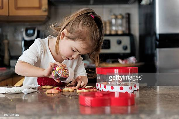Little girl making valentine's cookie
