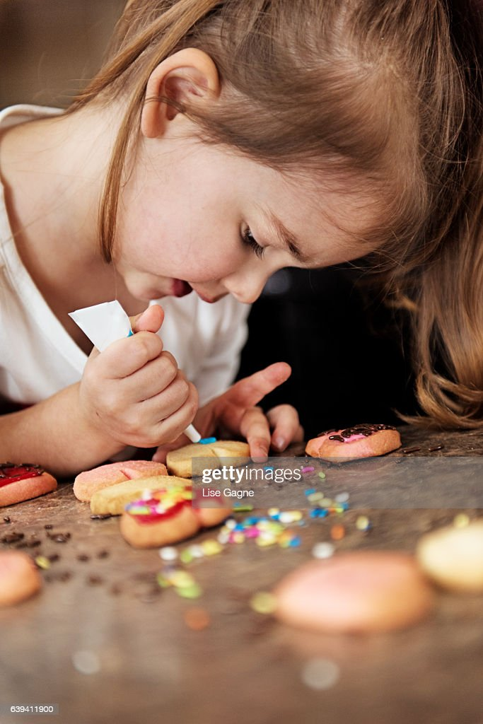 Little girl making valentine's cookie : Stock Photo