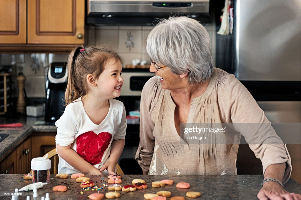 Little girl making valentine's cookie with grandma : Stock Photo