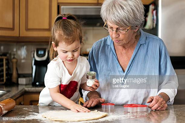 Little girl making valentine's cookie with grandma