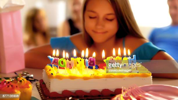 Little girl making wish at birthday pa