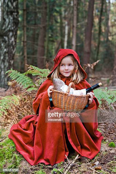 little girl masquerade as red riding hood sitting in the wood - hood clothing stock photos and pictures