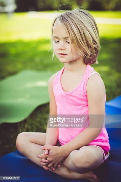 Little girl meditating outside in park.