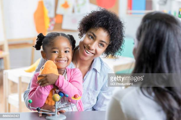 little girl meets new preschool teacher with mom - child care stock pictures, royalty-free photos & images