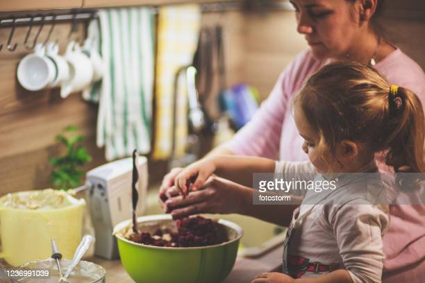 little girl mixing cherries in the cake batter with her mother - image foto e immagini stock