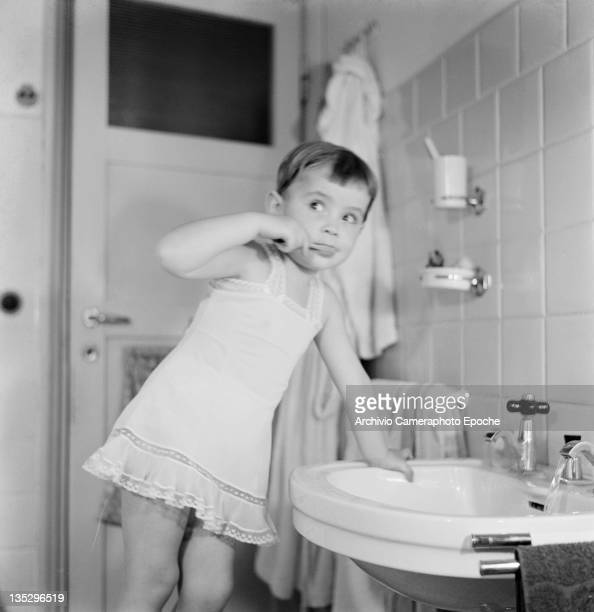 A little girl named Anarella brushes her teeth Italy circa 1965