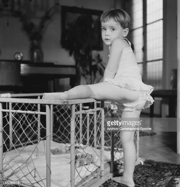 A little girl named Anarella climbs into her playpen Italy circa 1965