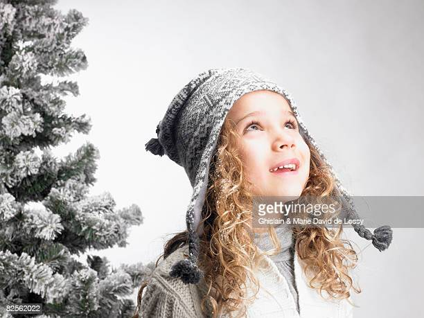 Little girl next to a fir-tree