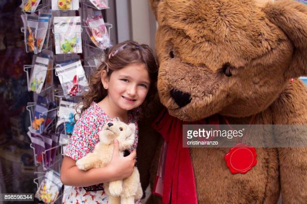 Little girl next to a huge bear