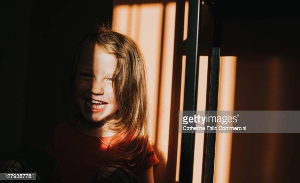 little girl obscured by a shadow, laughs while she confidently looks at the camera - unschuld stock-fotos und bilder