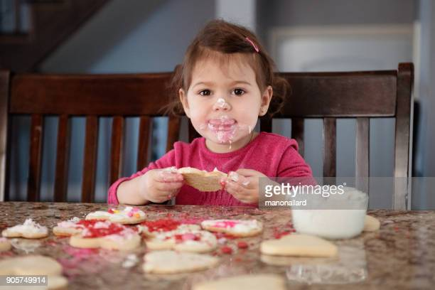 little girl of 2-3 years old taste cookies heart shape during valentine's day - 2 3 years stock pictures, royalty-free photos & images