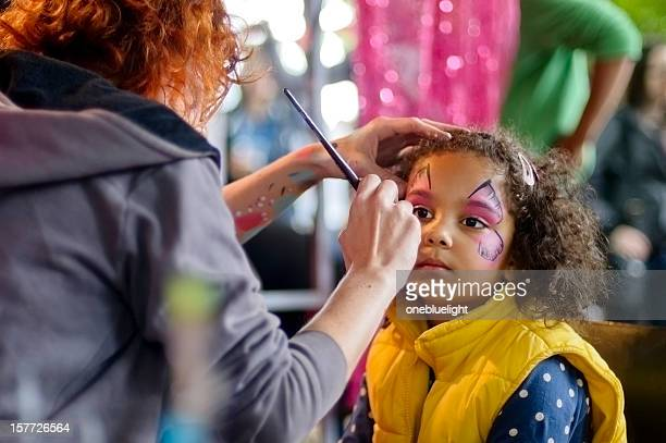 little girl of 5 is getting her face paint, outdoors - face paint stock pictures, royalty-free photos & images