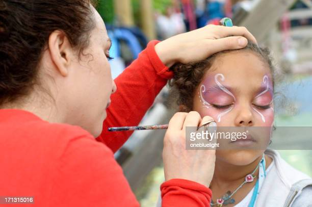 little girl of (6-7) is getting her face paint, outdoors - face paint stock pictures, royalty-free photos & images