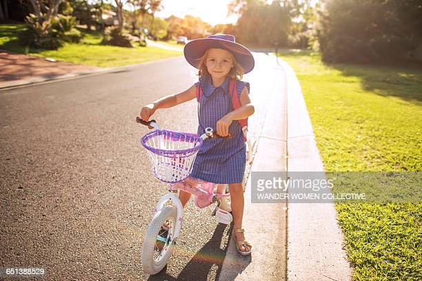 Little girl off to school in uniform on her bike