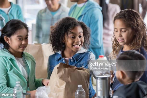 少女少年はフードバンクに水を提供しています - ホームレスシェルター ストックフォトと画像