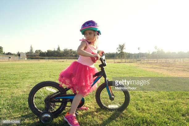Little girl on a bike wearing dress with tutu