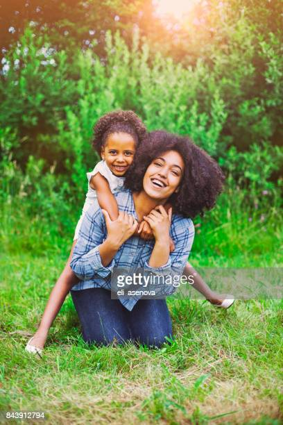 little girl on a piggy back ride with her mother in the park - black mothers day stock pictures, royalty-free photos & images