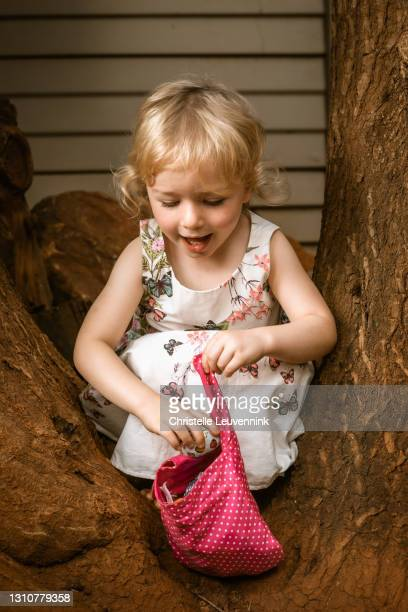 a little girl on an easter egg hunt - easter sunday stock pictures, royalty-free photos & images