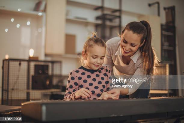 Little girl on piano class in music school