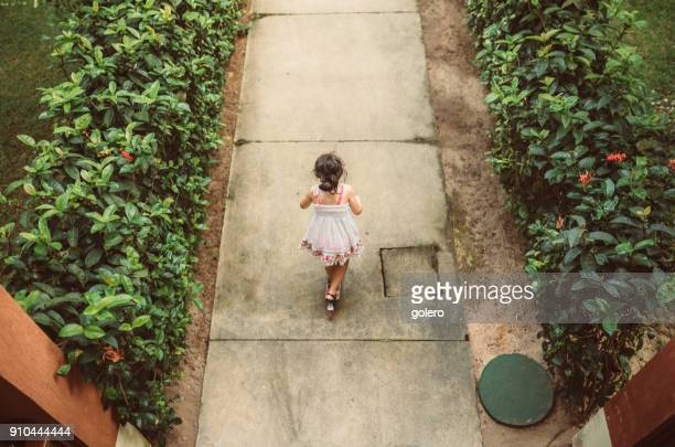 little girl on push scooter in the garden - little girls up skirt stock pictures, royalty-free photos & images