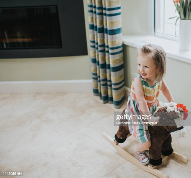 little girl on rocking horse - pony stock pictures, royalty-free photos & images
