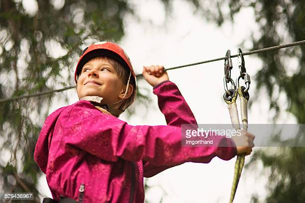 Little girl on ropes course in adventure park