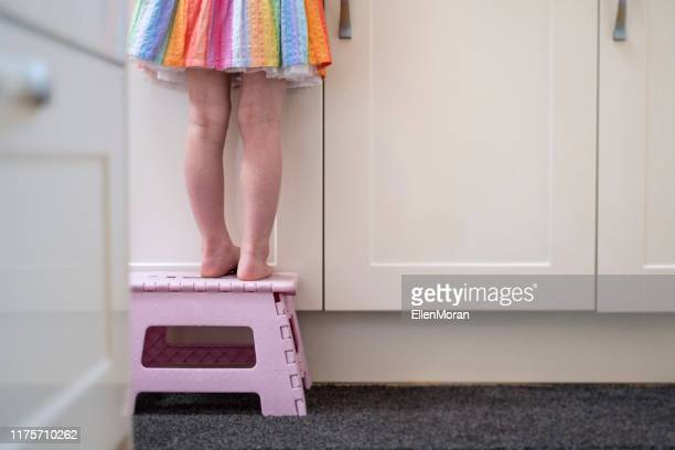 little girl on stool - step ladder stock pictures, royalty-free photos & images