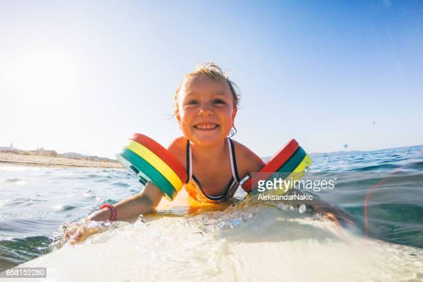 little girl on surfboard - armband stock pictures, royalty-free photos & images