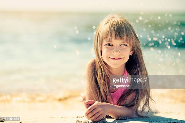 little girl on the beach. - little girl laying on the beach stock photos and pictures