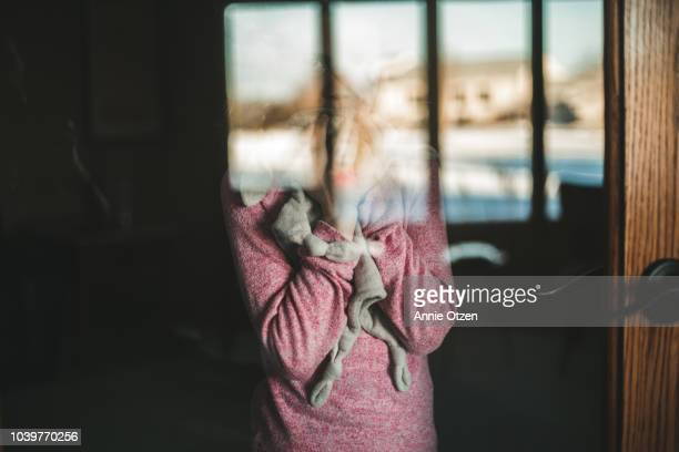 little girl on the other side of a glass door with her face obscured - onherkenbaar persoon stockfoto's en -beelden