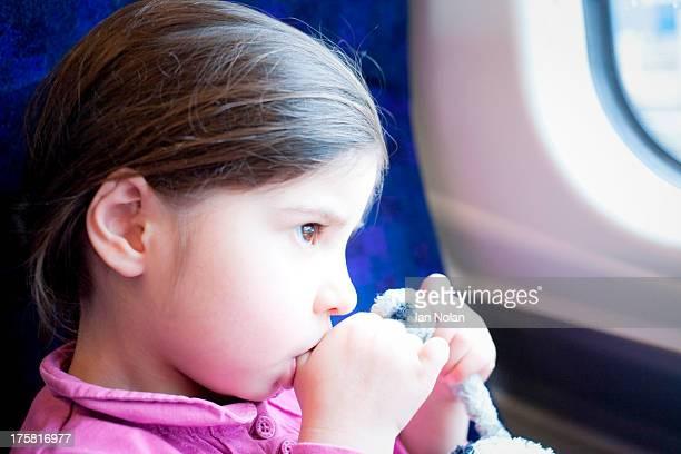Little girl on train, sucking thumb