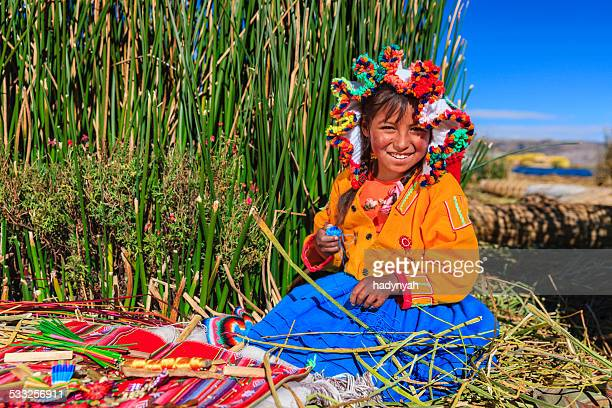 little girl on uros floating island selling souvenirs, lake tititcaca - bolivia stockfoto's en -beelden