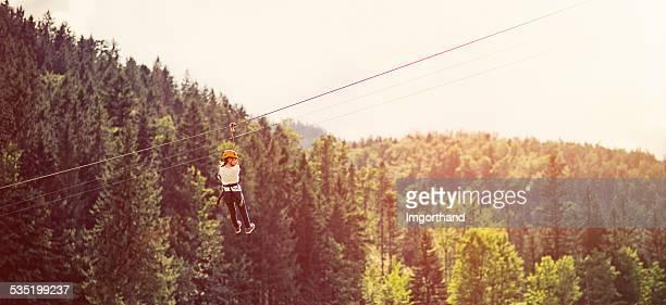 Little girl on tirolina en el parque de aventuras