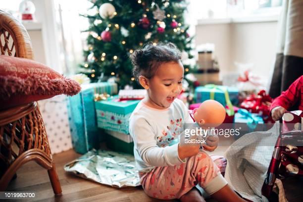 kleines mädchen öffnung geschenke am weihnachtsmorgen - puppe stock-fotos und bilder