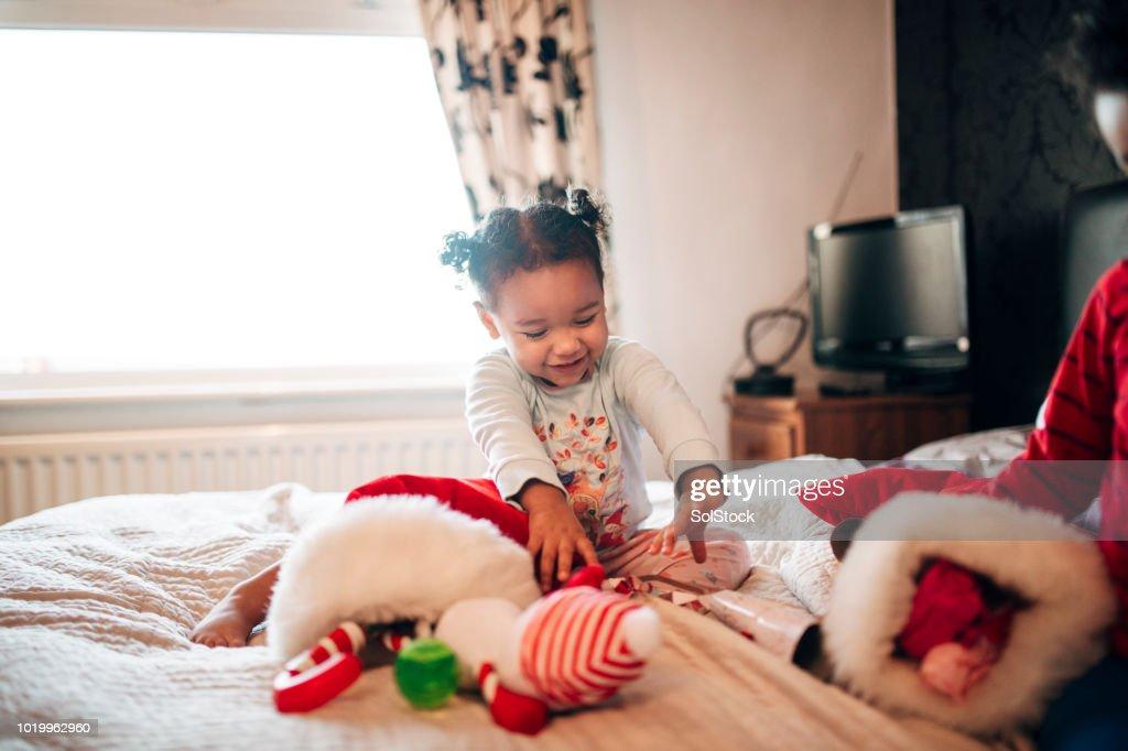 Little Girl Opening her Christmas Stocking on Christmas Morning : Stock Photo