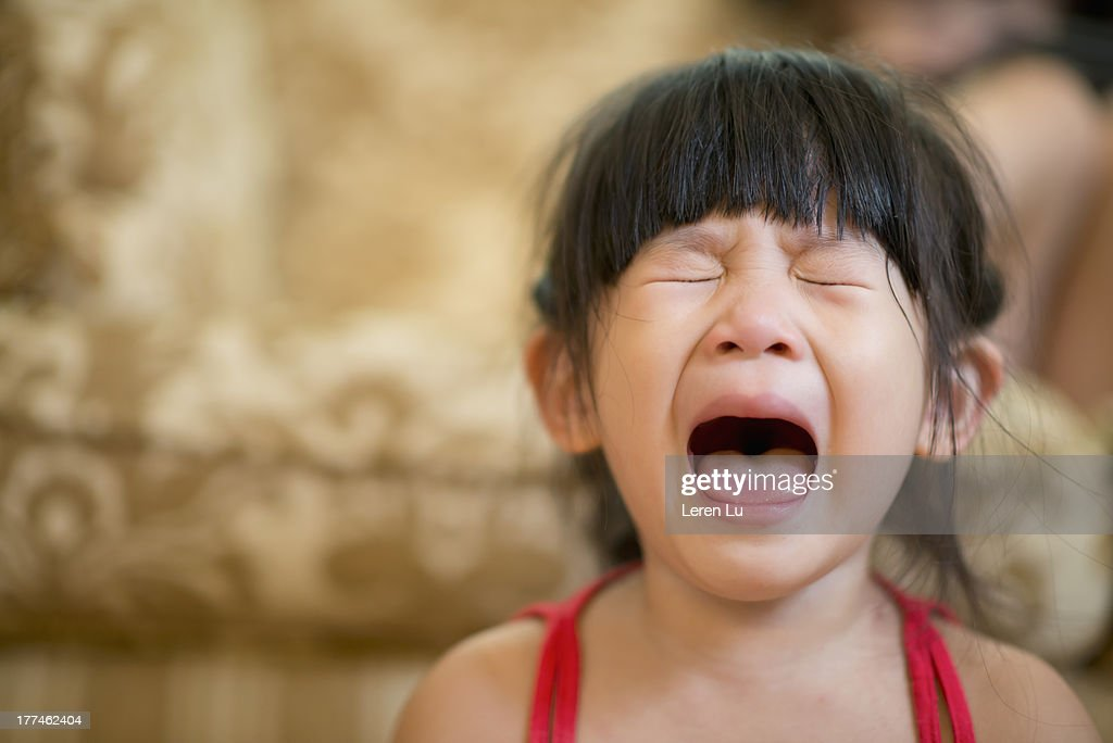 Little girl opening mouth and crying hysterically : Stock Photo