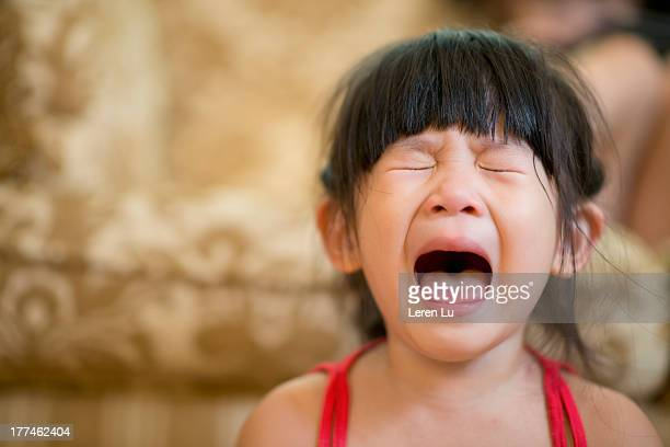 Little girl opening mouth and crying hysterically