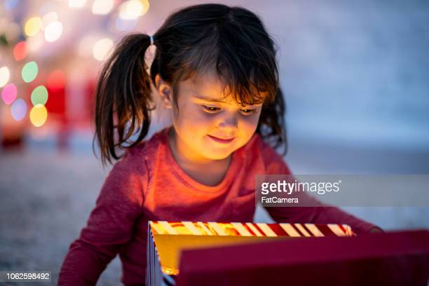 little girl opening present - fatcamera stock pictures, royalty-free photos & images