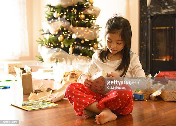 Little girl opening presents on Christmas morning