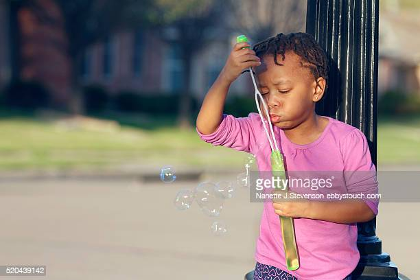 little girl outside blowing bubbles - nanette j stevenson stock photos and pictures