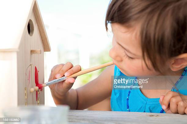 little girl painting birdhouse - birdhouse stock pictures, royalty-free photos & images