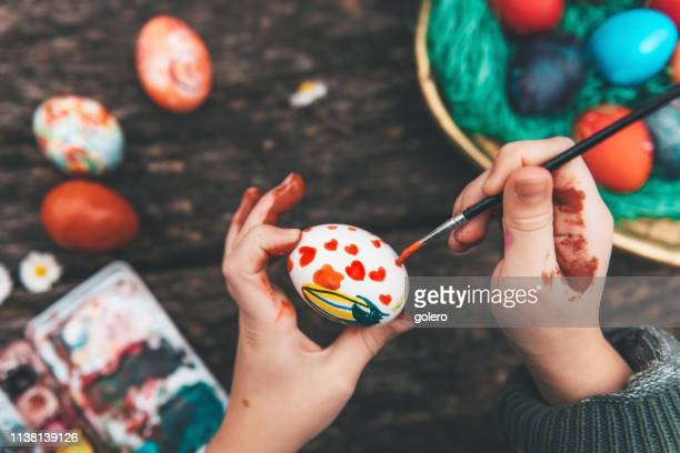 little girl painting easter egg on old wooden table - pasqua foto e immagini stock
