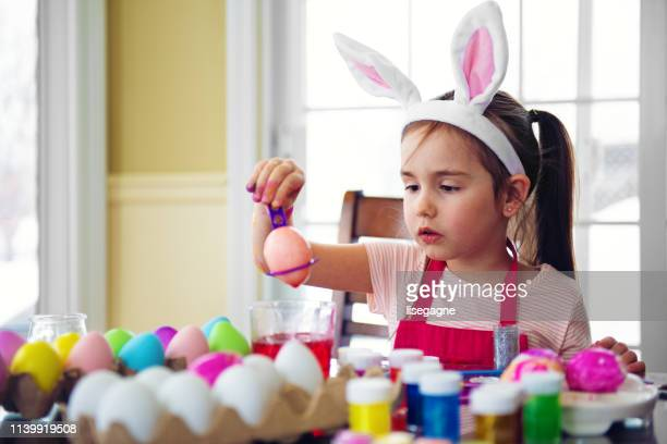 little girl painting easter eggs - dirty easter stock pictures, royalty-free photos & images