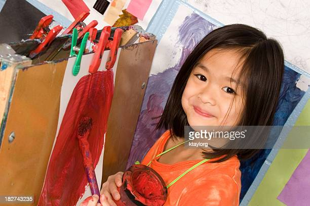 A little girl painting on an easel