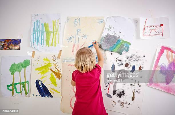 little girl painting on wall of children's room, rear view - zeichnen stock-fotos und bilder