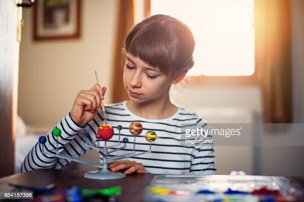 Little girl painting solar system model