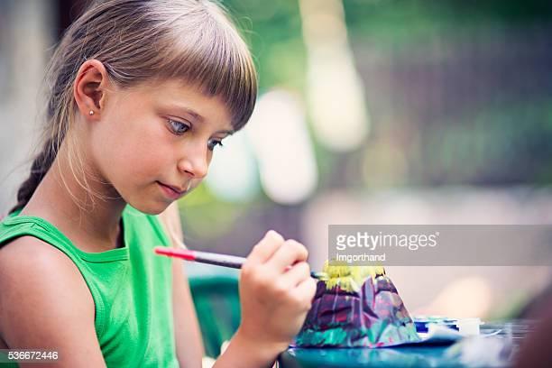 Little girl painting volcano school project